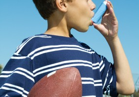 Asthmatic_boy_using_inhaler_holding_football_1