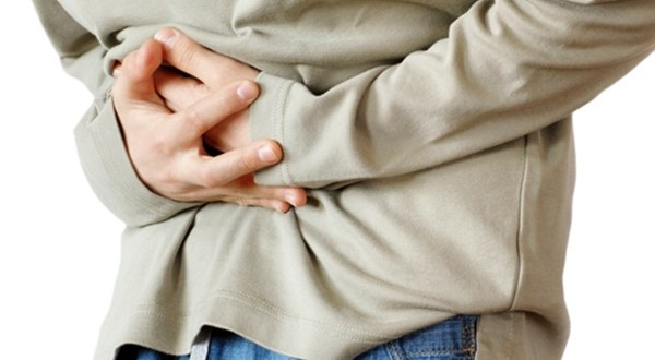 boy holding hands on his stomach over white background, pain